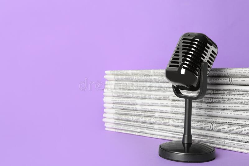 Newspapers and vintage microphone, space for text. Journalist`s work. Newspapers and vintage microphone on light violet background, space for text. Journalist`s royalty free stock image
