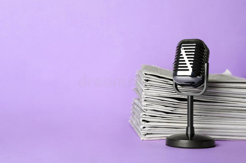 Newspapers and vintage microphone on light violet background, space for text. Journalist`s work royalty free stock images