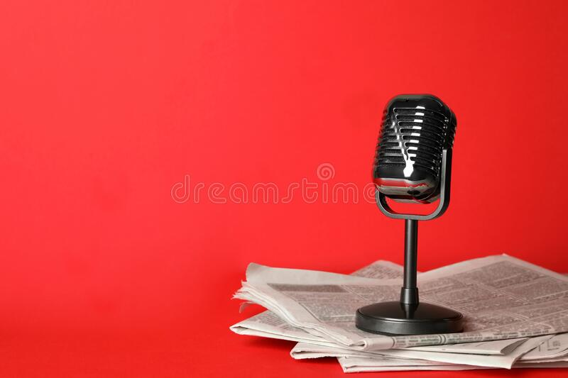 Newspapers and vintage microphone on red, space for text. Journalist`s work. Newspapers and vintage microphone on red background, space for text. Journalist`s stock photography
