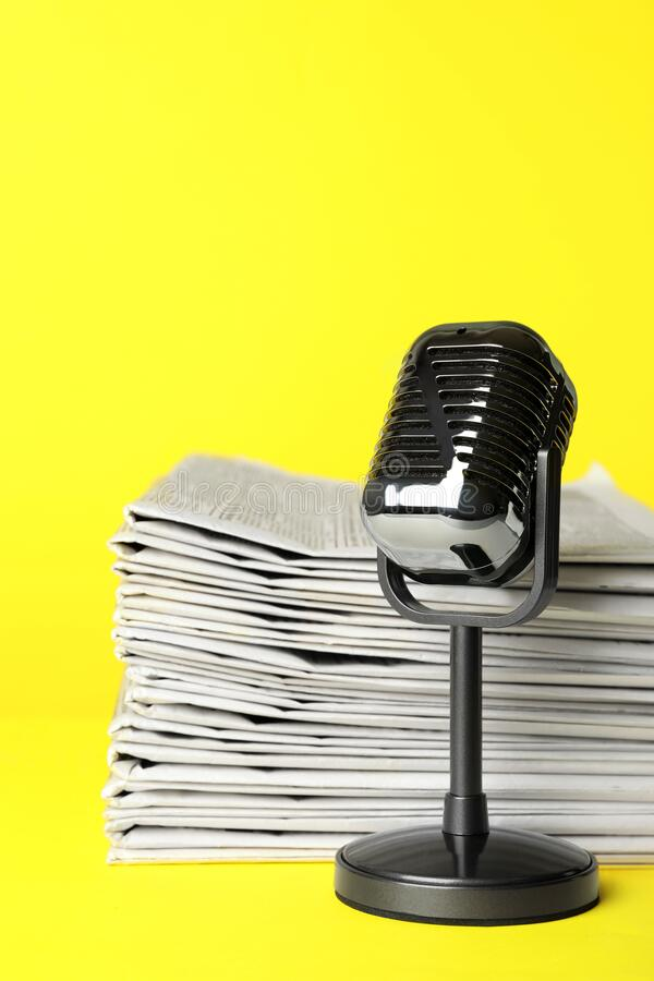 Newspapers and vintage microphone on yellow background. Journalist`s work stock image