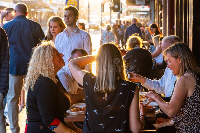 Newtown, Sydney, NSW - 27 10 2018: Friends eating al fresco at sunset royalty free stock photography