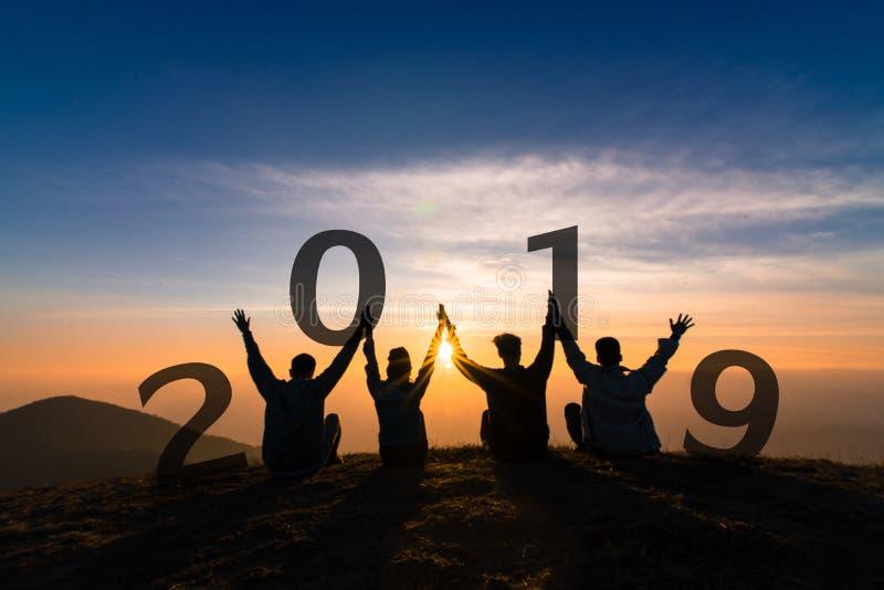 Newyear 2019年年轻朋友跳跃和手概念剪影  免版税库存图片