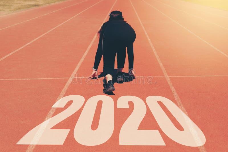 2020 Newyear, athl?te Woman commen?ant sur la ligne pour le d?but fonctionnant avec le d?but du num?ro 2020 ? la nouvelle ann?e photographie stock