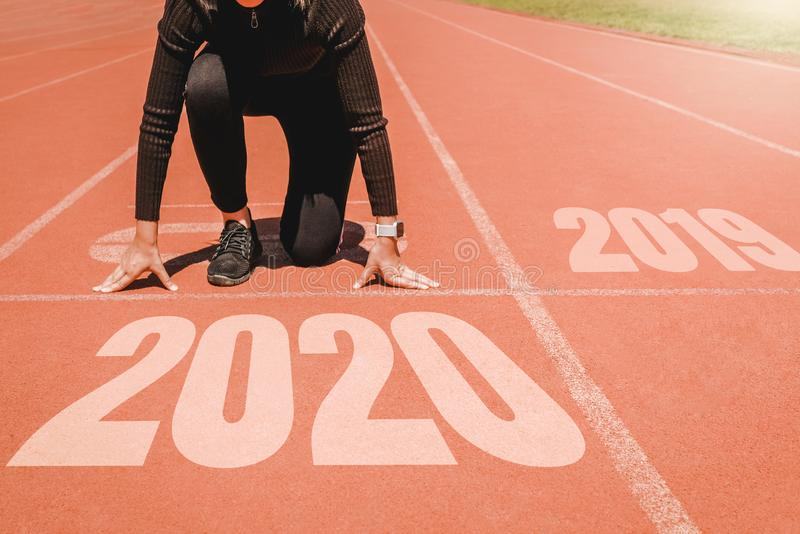 2020 Newyear , Athlete Woman starting on line for start running with number 2020 Start to new year stock image