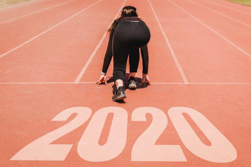 2020 Newyear, atleta Woman che inizia sulla linea per l'inizio corrente con l'inizio di numero 2020 al nuovo anno immagini stock