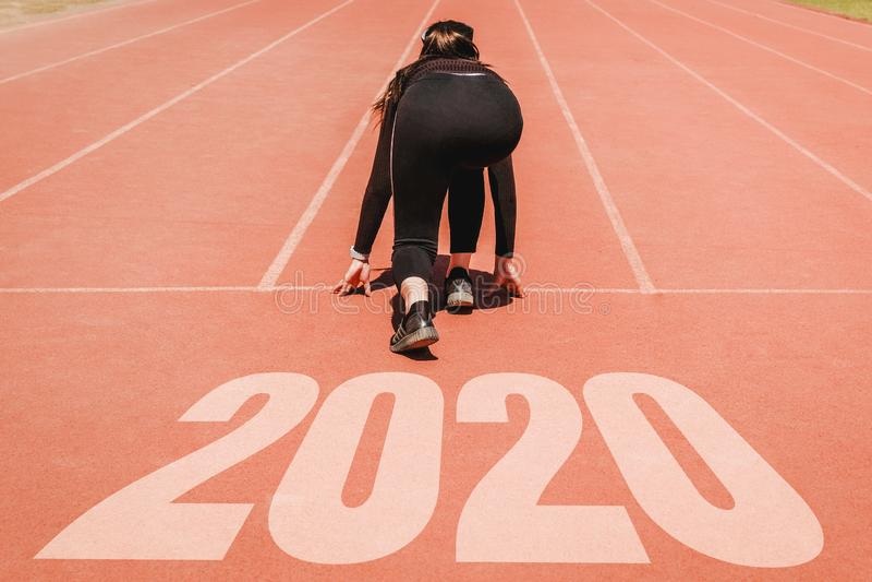 2020 Newyear, atleta Woman que comienza en la línea para el comienzo que corre con comienzo del número 2020 al Año Nuevo imagenes de archivo