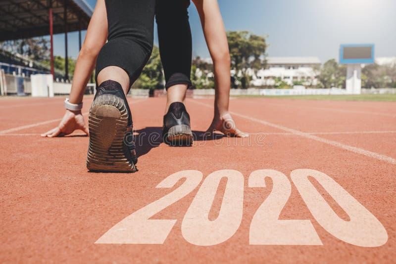 2020 Newyear, atleta Woman que comienza en la l?nea para el comienzo que corre con comienzo del n?mero 2020 al A?o Nuevo fotografía de archivo