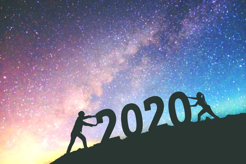 2020 Newyear  Couple tries to push number of 2020 Happy new year background on  the Milky Way galaxy royalty free stock photo