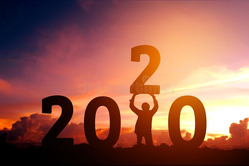2020 Newyear Man tries to Lift up number of 2020 Happy new year concept.  stock photography