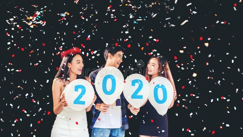 Newyear-Partei, Feierparteigruppe von den asiatischen jungen Leuten, die Ballonzahlen 2020 glückliches und lustiges Konzept halte lizenzfreie stockbilder