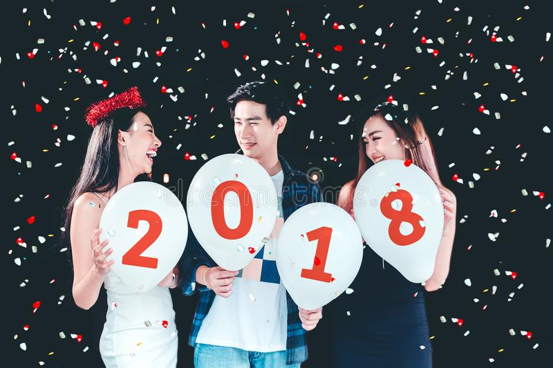 Newyear party ,celebration party group of asian young people holding balloon numbers 2018 happy and funny concept royalty free stock images