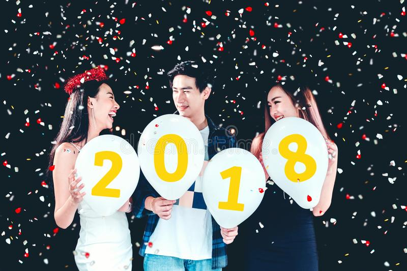 Newyear party ,celebration party group of asian young people holding balloon numbers 2018 happy and funny concept stock photos