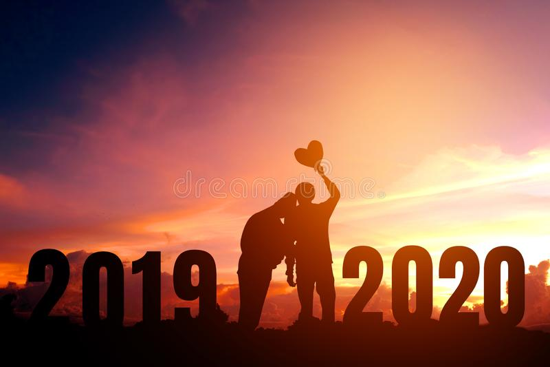 Newyear 2020 silhouettieren die jungen Paare, die f?r romantisches Konzept des neuen Jahres gl?cklich sind lizenzfreie stockfotografie
