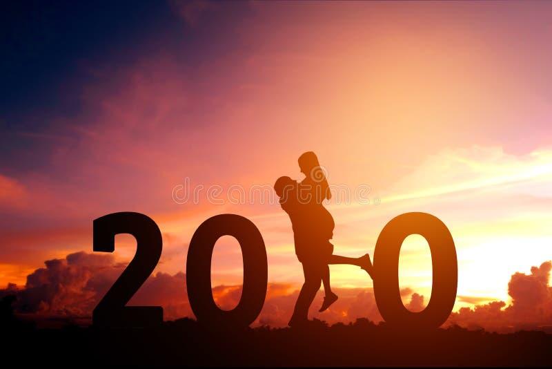 Newyear 2020 silhouettieren die jungen Paare, die f?r romantisches Konzept des neuen Jahres gl?cklich sind stockbilder