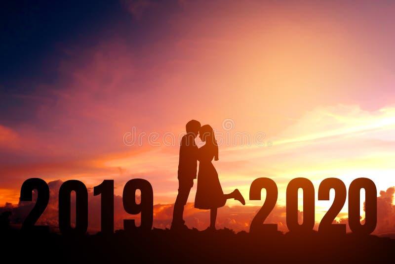 Newyear 2020 silhouettieren die jungen Paare, die f?r romantisches Konzept des neuen Jahres gl?cklich sind stockfotos