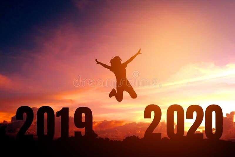 Newyear 2020 siluetea a la mujer joven que salta al concepto de la Feliz Año Nuevo imagenes de archivo