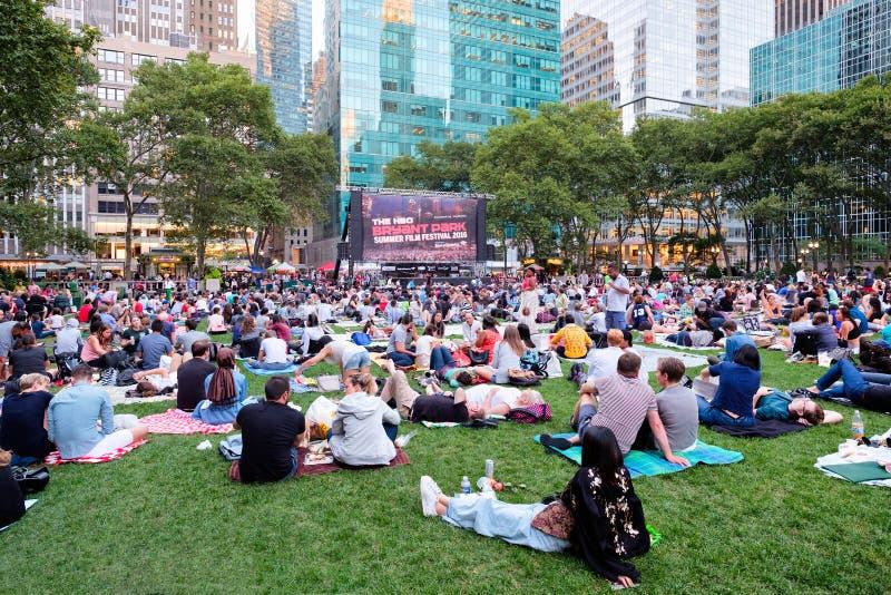 Newyorkers и туристы наслаждаясь Bryant паркуют фестиваль фильмов лета стоковые фото