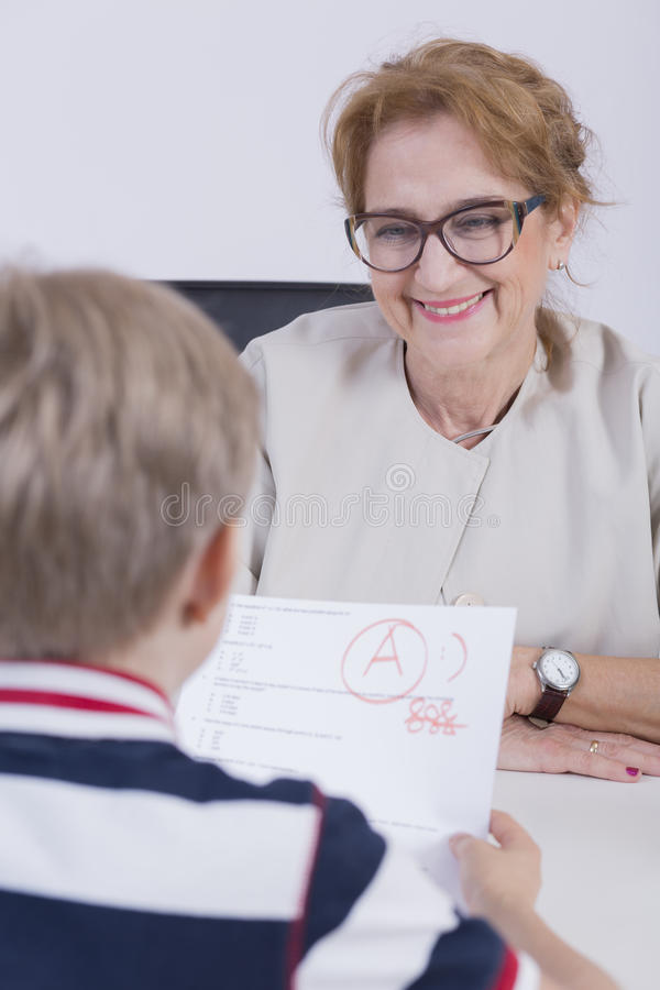 The next educational success. Smiled teacher looking at the pupil keeping the test with great mark stock image