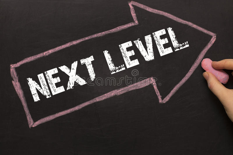 Next Level - female hand with chalk and arrow on blackboard stock photography