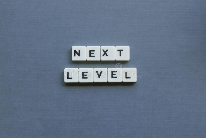 ' Next Level ' word made of square letter word on grey background. Concept, success, direction, forward, achievement, advance, business, text royalty free stock photo