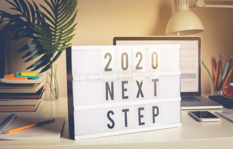 2020 next step text on light box on desk table in home office stock photo