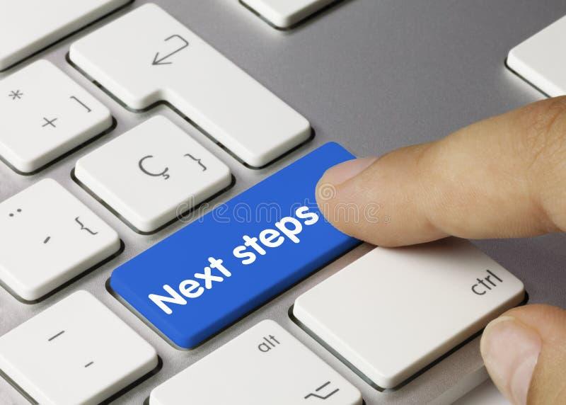 Next steps - Inscription on Blue Keyboard Key. Next steps Written on Blue Key of Metallic Keyboard. Finger pressing key royalty free stock photo