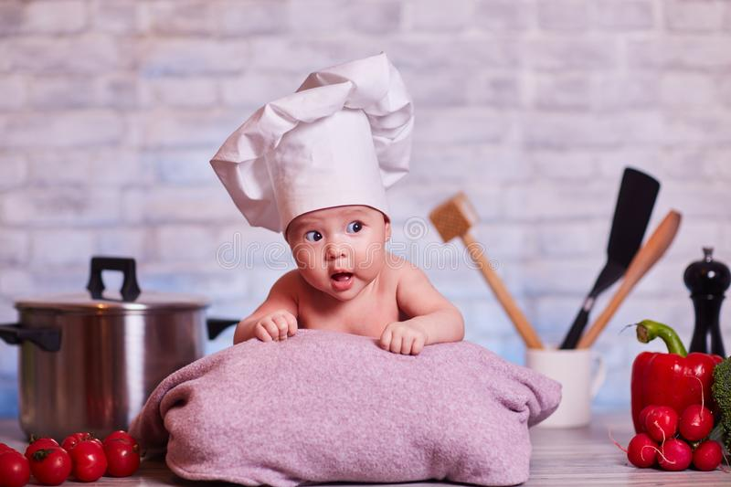 Child, baby girl lies on the kitchen table in a chef`s cap - next to him are vegetables, bell pepper, radish, broccoli, proper stock photography