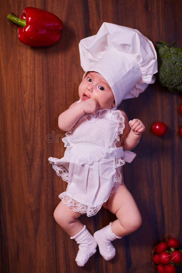 A child, baby, girl, lies on the kitchen table, in a cook`s cap and in an apron, in white socks, next to him lie vegetables, royalty free stock image