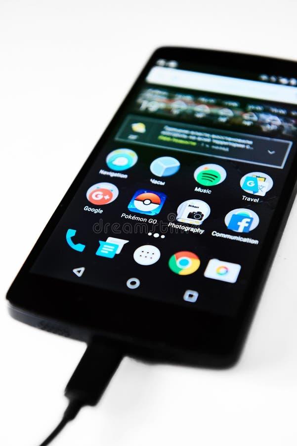 Nexus 5 smartphone charging. Riga, Latvia- July 17, 2016 : Nexus 5 smartphone charging. Close-up of a touch screen with application icons. Icons of Pokemon Go stock photography