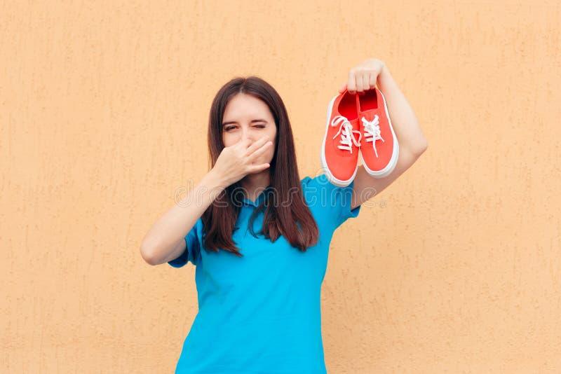 Nez de b?che de femme tenant une paire de chaussures Stinky photographie stock
