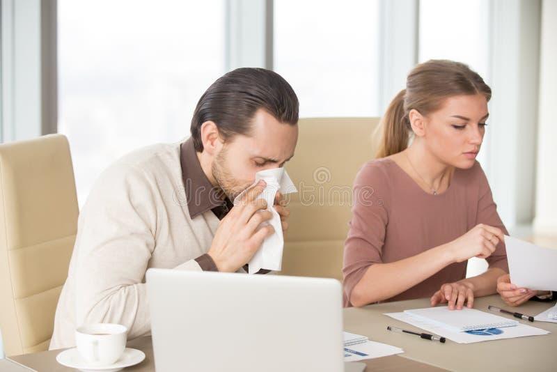 Nez de soufflement d'homme d'affaires fonctionnant dans le bureau avec des collègues, mers photo libre de droits