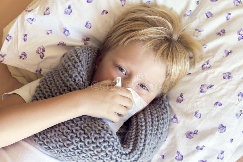 Nez de soufflement malade de garçon photographie stock