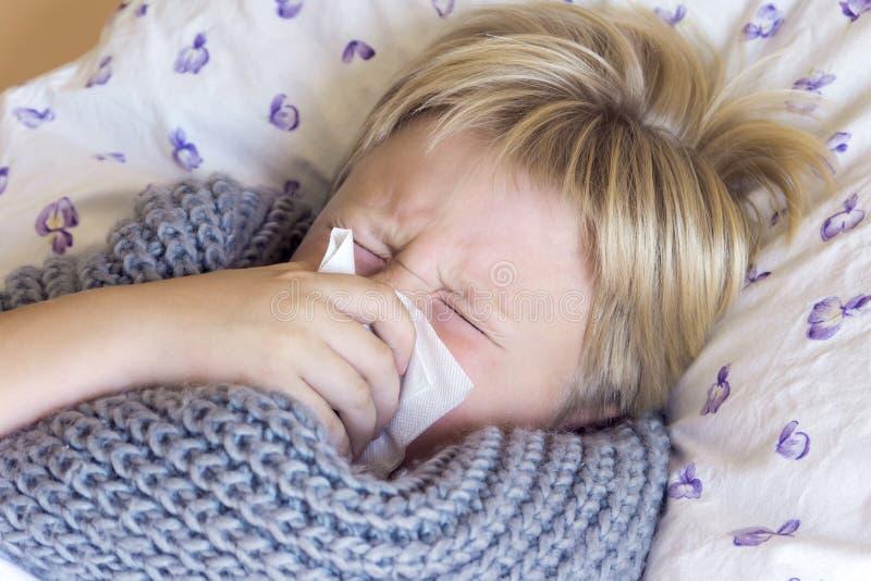 Nez de soufflement malade de garçon photo stock