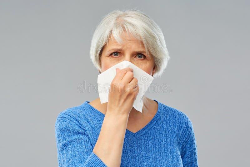 Nez de soufflement sup?rieur malade de femme ? la serviette de papier images stock