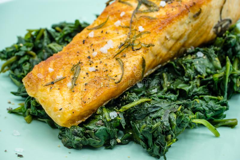 fried salmon with spinach on plate stock image