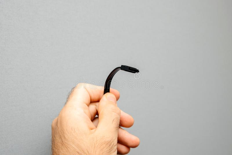 Ngineer holding new black S-ATA DATA Cable for HDD stock image