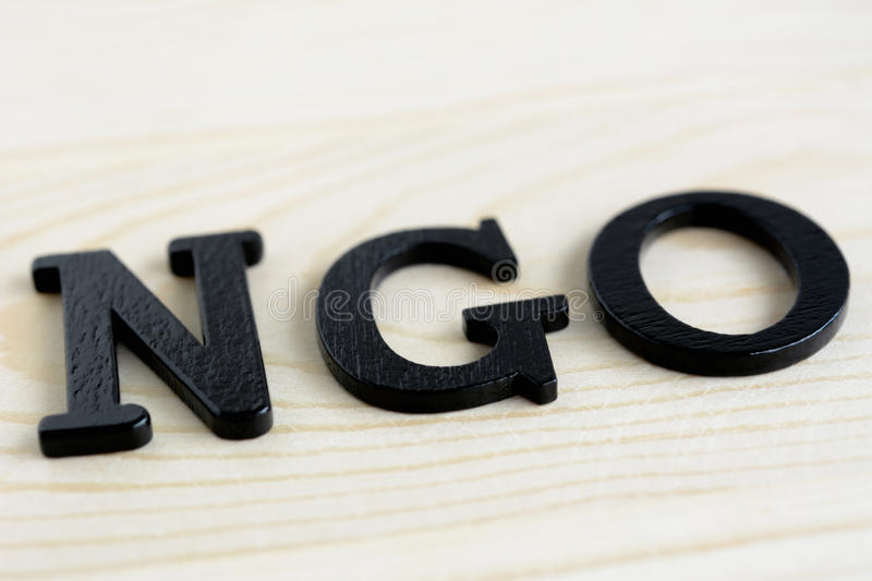 NGO letters on wood background. NGO stand for Non-Governmental Organization stock images