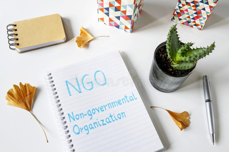 NGO Non-Governmental Organization written in notebook. On white table stock images
