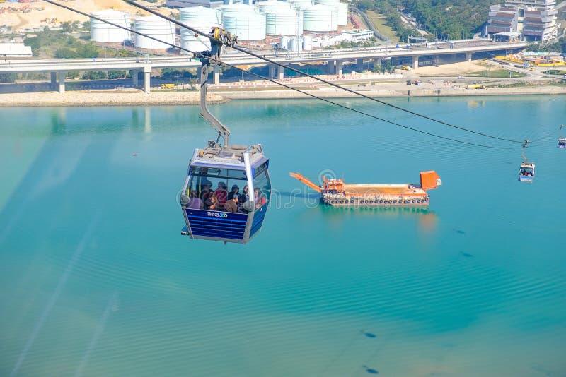 Ngong Ping Cable bil med turister över hamn, berg och stadsbakgrund, att besöka Tian Tan eller den stora Buddha som lokaliseras p royaltyfria bilder