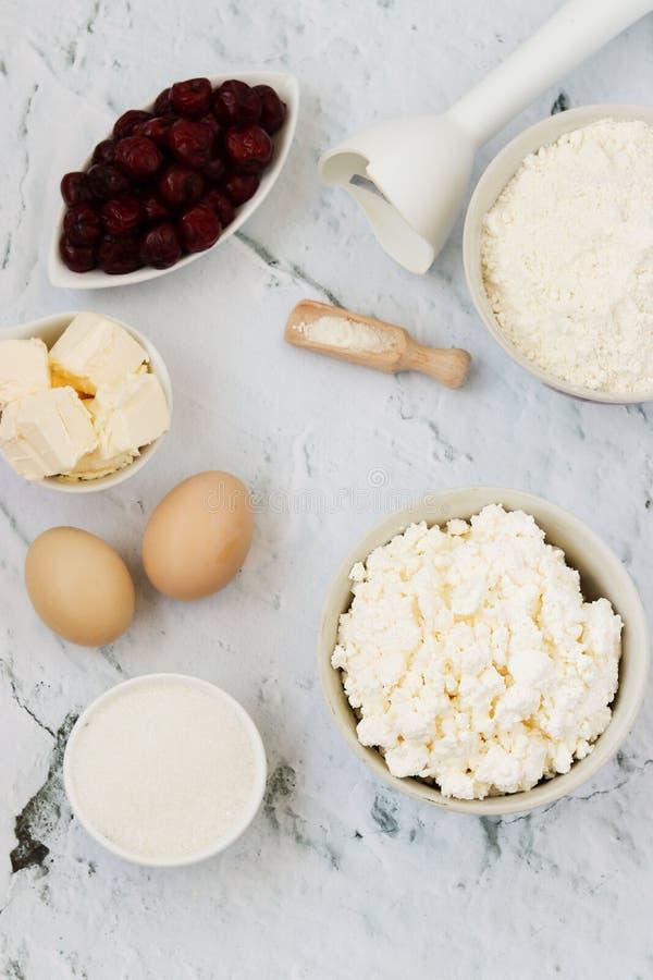 Ngredients för förberedelsen av ostmassakakan med körsbär: mjöl, bakpulver, ägg, keso, smör, socker och körsbär royaltyfri bild
