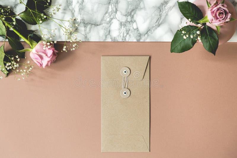 Ângulo alto da mesa cor-de-rosa e de mármore suja com rosas frescas, o envelope de papel e espaços vazios para seus cadernos e pe fotos de stock