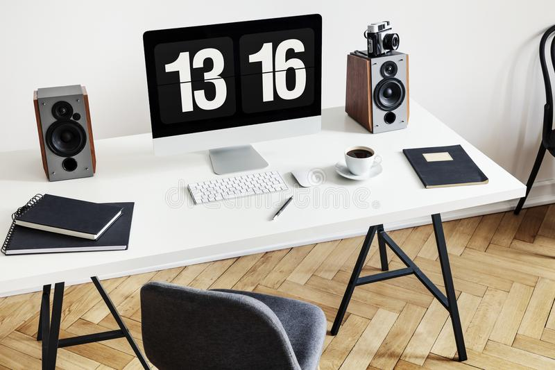 Ângulo alto de uma mesa com um computador, os cadernos, os oradores e o teclado ao lado de uma cadeira em um interior do escritór imagens de stock