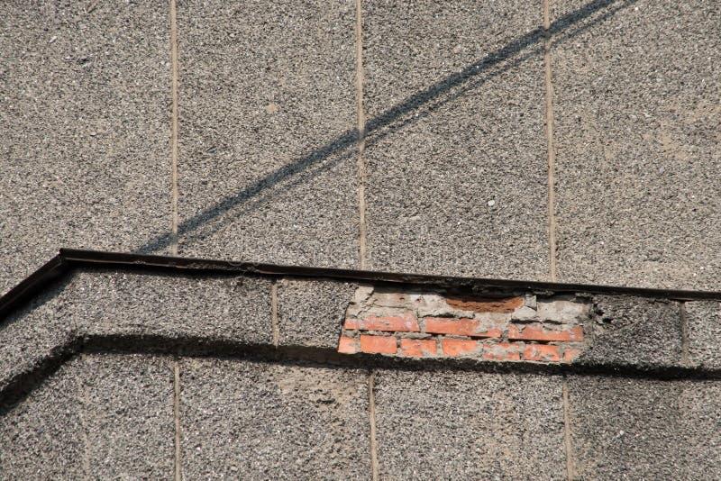 Ângulo de uma parede cinzenta de desintegração da casa fotografia de stock