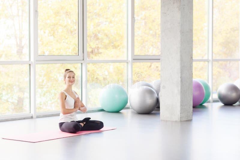 Ângulo encadernado, postura dos lótus Mulher que faz a ioga, olhando a câmera imagens de stock royalty free