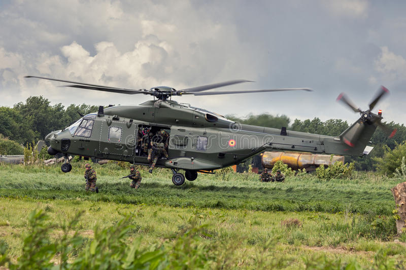 NH-90 helicopter landing soldiers stock image