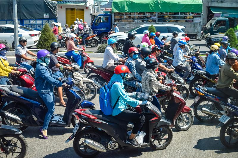 NHA TRANG, VIETNAM - APRIL 13, 2019: Plenty motorcyclists drive on road in rush hour on day. NHA TRANG, VIETNAM - APRIL 13, 2019: Plenty motorcyclists drive on royalty free stock photo