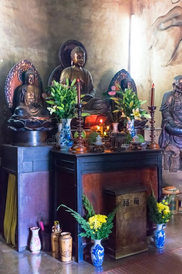 NHA TRANG, VIETNAM - APRIL 13, 2019: Statue of buddha with flowers and candles in temple royalty free stock photography