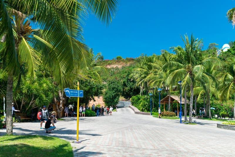NHA TRANG, VIETNAM - 16 APRILE 2019: Turisti nel parco di divertimenti sotto gli alberi tropicali in Vinpearl in Nha Trang fotografia stock libera da diritti