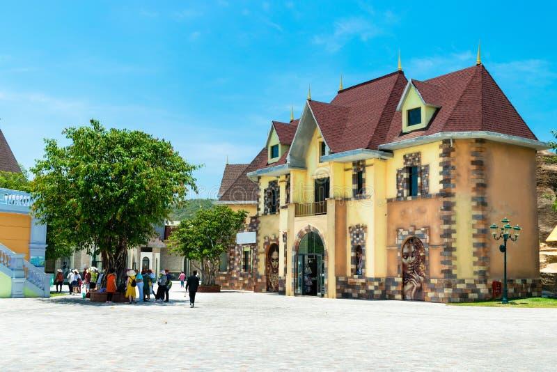 NHA TRANG, VIETNAM - 16 APRILE 2019: Turisti sotto un albero in un parco di divertimenti con una bella costruzione in Vinpearl immagine stock