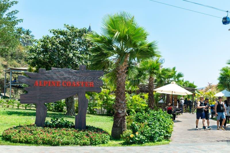 NHA TRANG, VIETNAM - 16 AVRIL 2019 : Touristes en parc d'attractions tropical avec un signe et paume dans Vinpearl au Vietnam images libres de droits